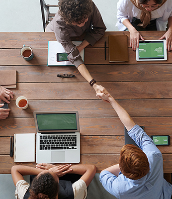 business team at table with two people shaking hands over financial strategic advising